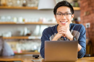 Person with glasseslooking up from their laptop and smiling