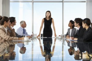 Woman standing at end of conference table addressing a group seated at the table